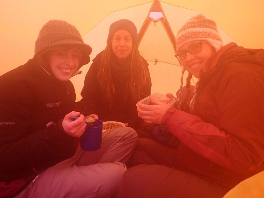 Hele gruppen har søgt ly for uverjret og spiser aftensmad i Alines telt. Foto: Aline Boer.